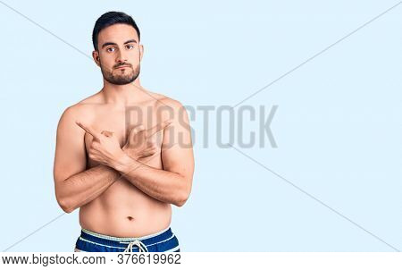 Young handsome man wearing swimwear pointing to both sides with fingers, different direction disagree