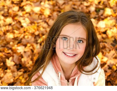 Autumn Portrait Of Adorable Smiling Little Girl Child In Leaves In The Park Outdoors Closeup