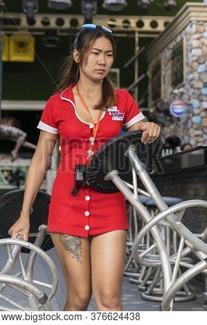Thailand, Phuket, April 15, 2020: Sexy Thai Waitress, Night Club Worker, Arranges Furniture In The B