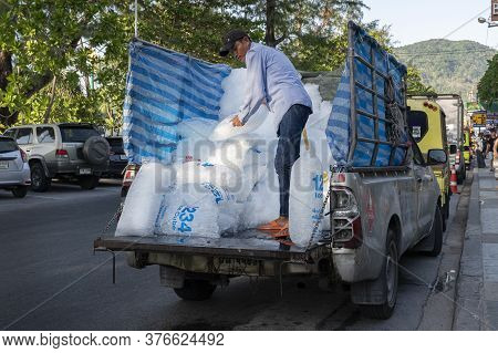 Thailand, Phuket, April 15, 2020: A Worker Unloads Ice Delivered To Bars And Restaurants From A Pick