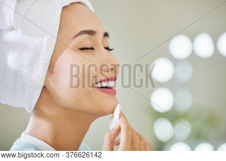 Happy Young Asian Woman Enjoying Applying Refreshing Soothing Treatment Lotion On Her Face With Cott