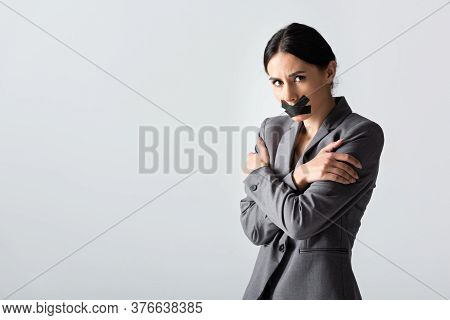Businesswoman With Scotch Tape On Mouth Standing With Crossed Arms Isolated On White, Gender Inequal
