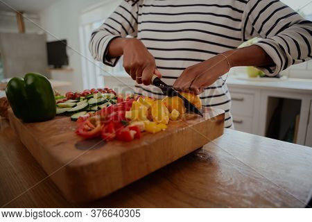 Closeup Of Woman Hands Chopping Yellow And Red Bell Peppers On Wooden Chopping Board In Modern Kitch