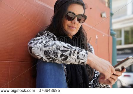 Trendy woman standing on brick wall in town