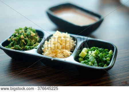 Set Of Slice Vegetable, Garlic, Chill And Chives On Black Tray For Topping Sauce In Shabu Style