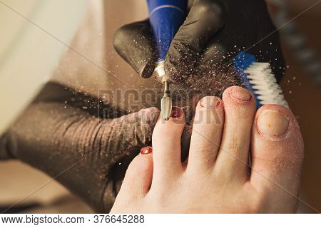 Professional Making Pedicure Removing Old Coating In Salon. Master Chiropody Shapes The Nails. Femal