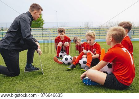 Group Of Sad Boys With Coach After Loosing Soccer Tournament Match. Kids Listening To Junior Level S