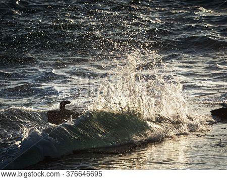 Wavy Spray Crashing Mooring Pin For Medium Boats. Rusty Bent Mooring Bollard In A Port.