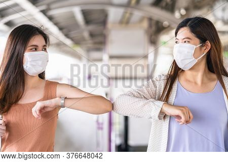 Young Asian Woman Passenger Wearing Surgical Mask And Elbows Bump With Friend Together In Subway Tra