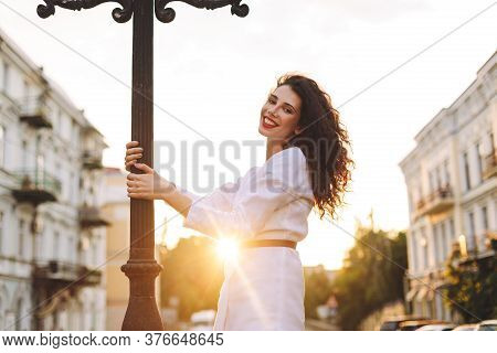 Young Smiling Lady In White Jacket Standing On Street And Joyfully Looking In Camera With Beautiful