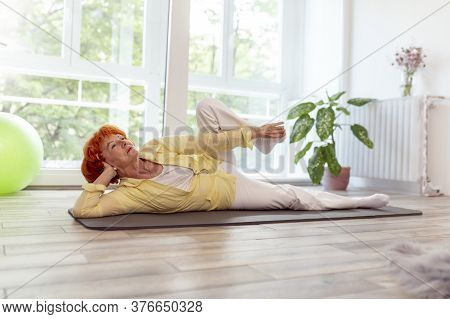 Active Senior Woman Doing Yoga Training And Relaxing At Home, Enjoying Her Leisure Time - Healthy An