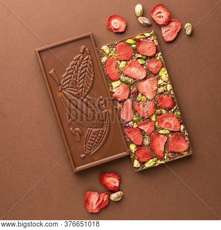 Chocolate Milk Belgian Bar With The Addition Of Pistachio Strawberries On A Brown Background. Desser