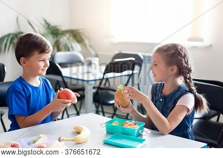 School Kids Eating Healthy Food Together. Happy Children Sitting At Table With Packed Lunch Boxes. B