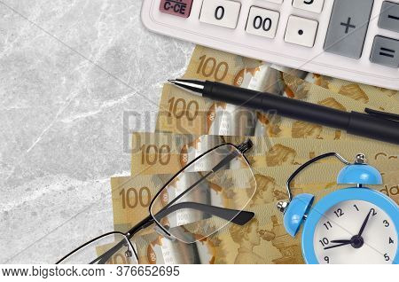 100 Canadian Dollars Bills And Calculator With Glasses And Pen. Business Loan Or Tax Payment Season