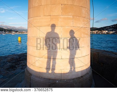 Traveling Couple Play With Own Shadows On  Lighthouse Wall,  Port De Andratx In Majorca. Man And Wom