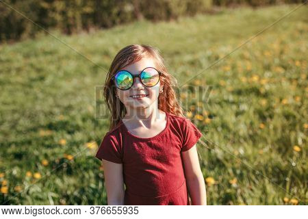 Happy Smiling Young Caucasian Girl In Funny Sunglasses Posing Outdoor. Cute Adorable Kid Child Havin