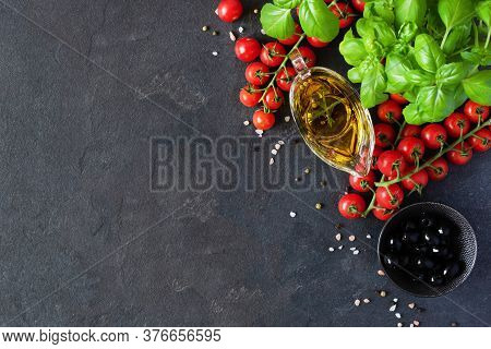 Olive Oil In A Glass Sauceboat, Cherry Tomatoes And Basil On Black Background Top View.