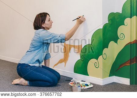 Caucasian Woman Artist Hand Painting Murals On Walls Indoor At Apartment Or Studio School With Acryl