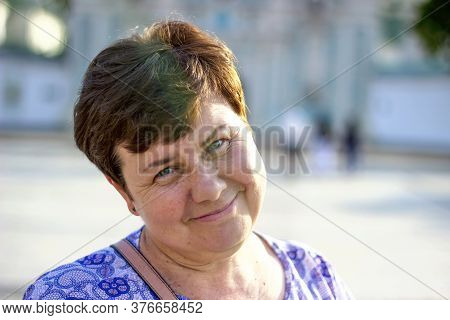 A Beautiful, Happy, Smiling, Middle-aged Woman With Short Hair. With A Wide Smile, Looks To The Far