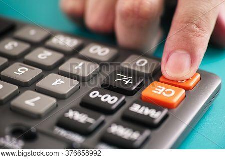 A Finger Pressing A Calculator Key. Close Up.