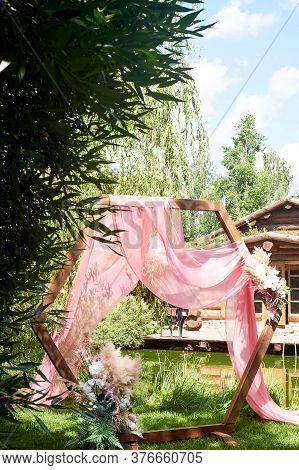 Check-in In The Forest By The Lake. A Diamond-shaped Arch Of Wood Decorated With Pampas, Pink Chiffo