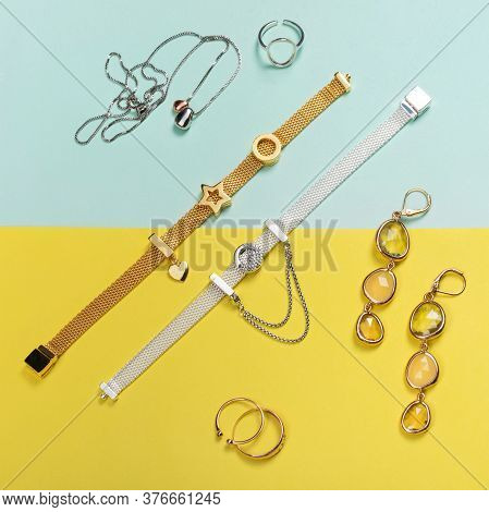 Silver And Gold Jewelry On Minimal Yellow And Blue Background. Rings, Bracelets, Earrings And Neckla
