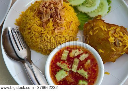 Top View Of Biryani Rice With Chicken In Thai Style Served With Cucumber And Sweet And Spicy Sauce.