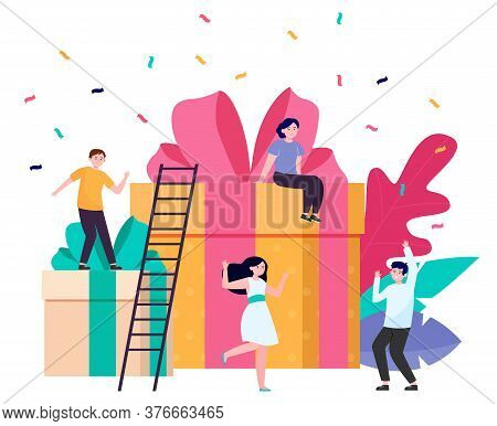 Group Of Friends Having Fun At Surprise Party. Cheerful People Dancing Among Gift Boxes An Confetti,