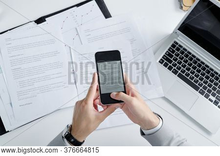 Above view of unrecognizable lawyer using smartphone while photographing contract papers on table