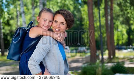 A Beautiful Caucasian Woman Stands Outdoors And Holds Daughter On Her Back. A Cheerful Smiling Girl