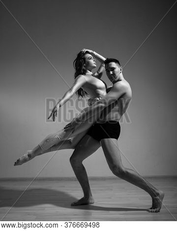 A Man And A Woman Are Dancing Modern Ballet. Acrobatic Couple Perform Number On A White Background.