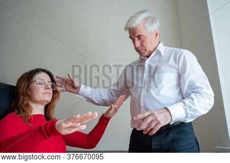 An Elderly Man Hypnotizes A Female Patient. A Woman In A Session With A Male Hypnotherapist During A