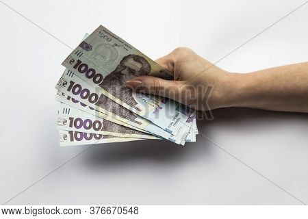 Female Hand Holds A Five Thousand Hryvnia. Ukrainian Currency With Woman's Hand Against A White Back