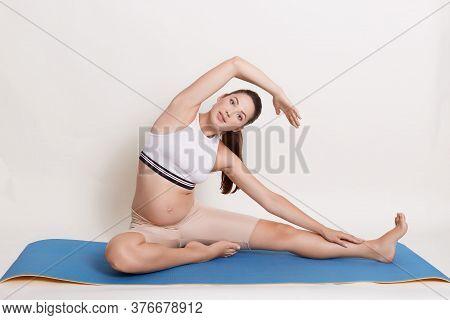 Pregnant Yoga Prenatal Maternity Doing Different Exercises While Sitting On Blue Mat, Breathing, Str
