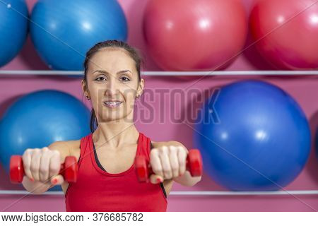 Portrait Of A Young Woman Doing Exercises With Dumbbells In A Gym