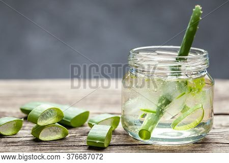 Aloe Vera Gel Cream For Skin And Body Care. Aloe Pulp Slices In A Glass Jar And Leaves On A Wooden T