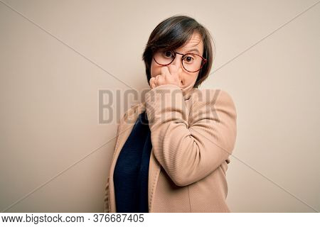 Young down syndrome business woman wearing glasses standing over isolated background smelling something stinky and disgusting, intolerable smell, holding breath with fingers on nose. Bad smell