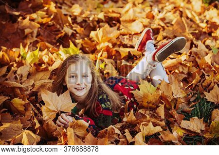 Kid Girl Lying On Leaves. Adorable Little Girl With Autumn Leaves In The Beauty Park. Funny Kids Out