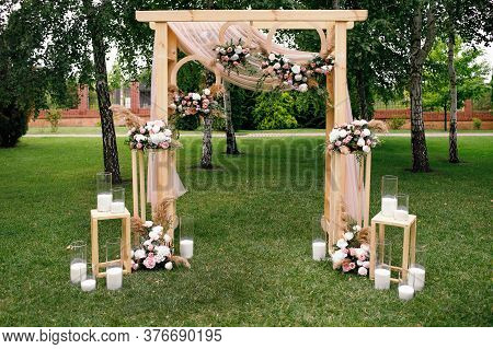 Wedding. Ceremony. Wedding Arch. Wedding Arch Of Flowers And Greenery Stands On The Green Grass In T