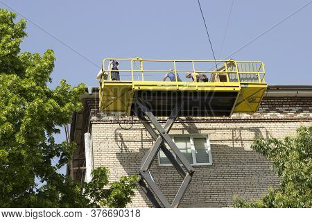 Builders Are Repairing The Roof Of A Multi-storey Building, Workers Are In A Construction Cradle, In
