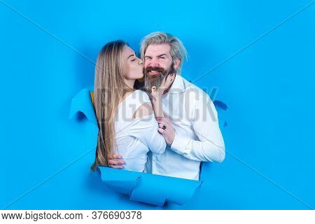 Fashionable Happy Couple On Blue Background. Young Couple Kissing Through Paper. Surprised Man And W