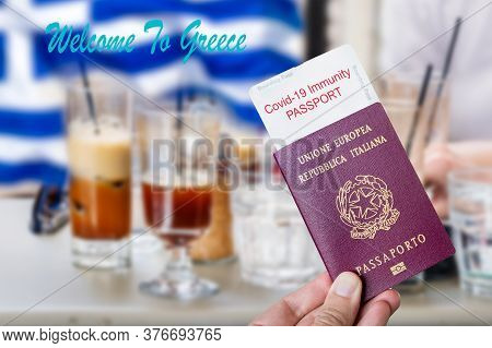 Male Hand Holding An European Passport With A Covid-19 Immunity Certificate Over The Greek Flag Cold