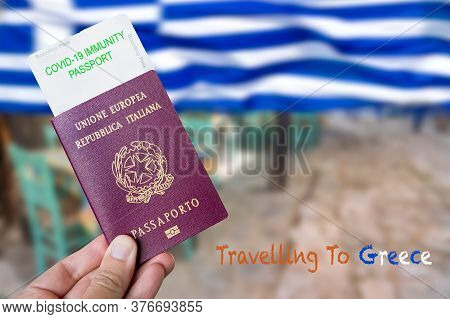 Male Hand Holding An European Passport With A Covid-19 Immunity Certificate Over The Greek Flag Back
