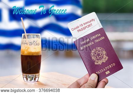 Male Hand Holding An European Passport With A Covid-19 Immunity Certificate Over The Greek Flag And