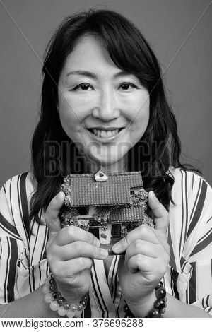 Portrait Of Mature Beautiful Asian Businesswoman With House Figurine