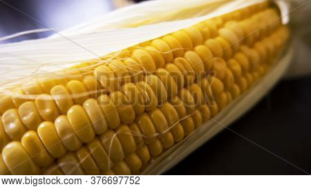 A Closeup Shot Of Raw Maize Corns & Leaves On Dark Background
