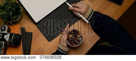 Female Hand Holding Ice Coffee Mug While Working With Mock Up Digital Tablet On Wooden Table