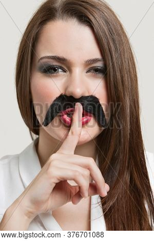 Portrait of young woman with fake mustache gesturing to be quiet over gray background