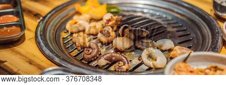 Woman Grilling Barbecue On Mesh Grill Of Charcoal Fire. Korean Or Japanese Traditional Food Grilling
