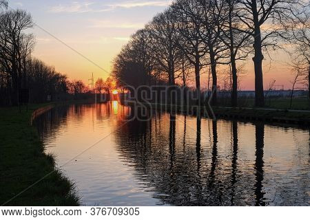 Panorama Of A Gorgeous Scenic Sunset At A River Or Canal, With Gold And Blue Color In The Sky And Th